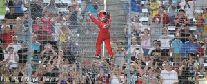 Helio Castroneves climbs the fence to celebrate his Texas victory