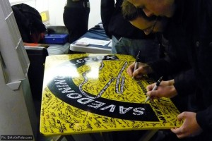 Supporters sign a 'Bubble and Kick' racing Porsche roof panel