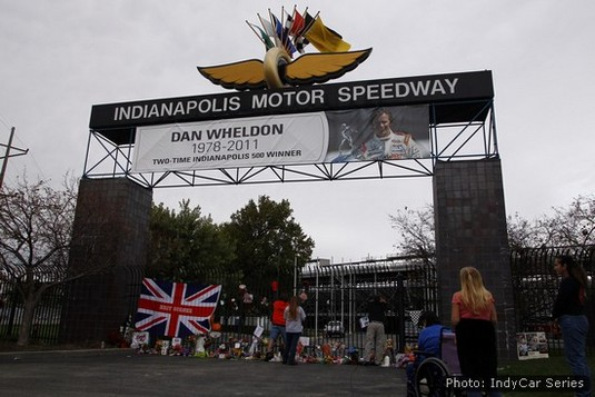 Fans gather to lay tributes beneath the memorial banner at the Indianapolis Motor Speedway
